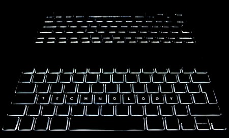 backlit keyboard: TECHNOLOGY is spelled out on a backlit keyboard with reflection Stock Photo