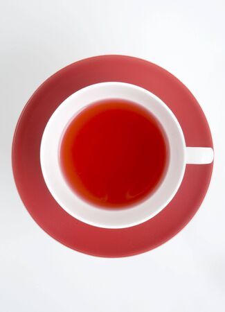 Rosehip(red) tea in a white cup on red saucer photo