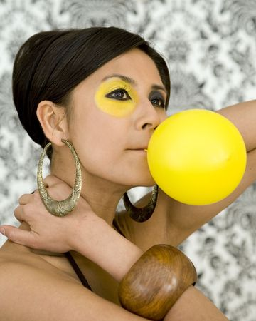 nouse: Beautiful asian model with funky make-up blow balloon Stock Photo
