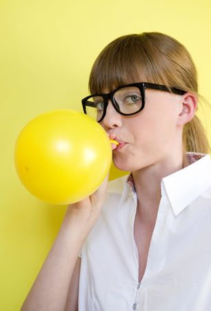 nouse: Young pretty girl blows up a balloon