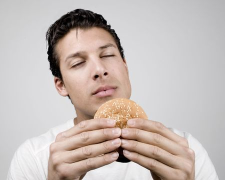 smells: Young man smells a tasty big burger
