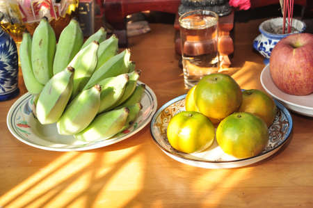 Raw Namwa Banana Oranges and apples in the plate on the wooden table