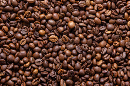 Coffee beans texture. Brown background with roast grains. Top view.