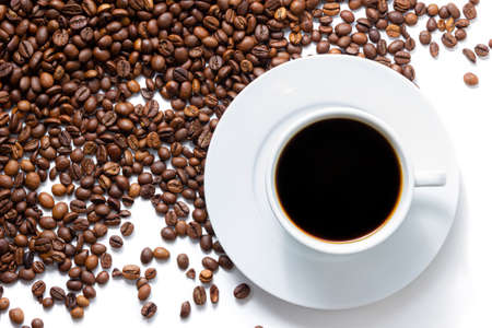 A cup of coffee with beans on white background. Top view of roast grains.