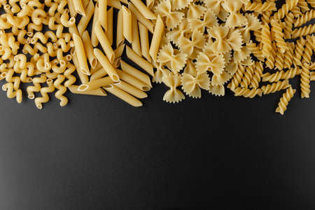 Different kinds of raw pasta with copy space on black background. Top view of Italian cuisine ingredient.