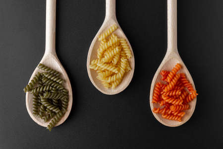 Raw pasta torti on wooden spoons on black background. Top view of Italian cuisine ingredient.