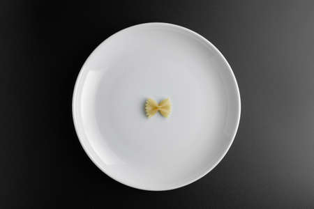 Raw pasta farfalle on plate on black background. Top view of Italian cuisine ingredient.