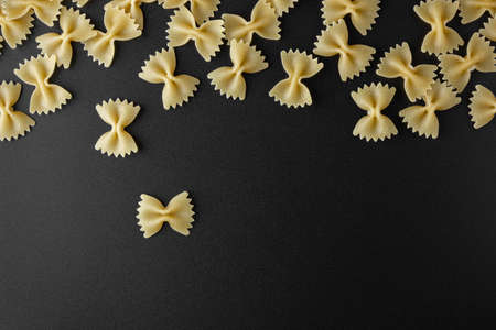 Raw pasta farfalle with copy space on black background. Top view of Italian cuisine ingredient.