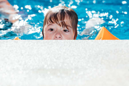 Little blond-haired girl in the pool wearing sleeves, peeking out from the curb