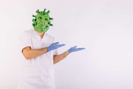 Person disguised as virus with latex mask - virus, wearing doctor's suit, holding large syringe, on white background.