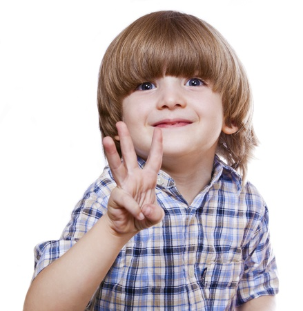 smiling little boy shows three fingers on a white background  photo