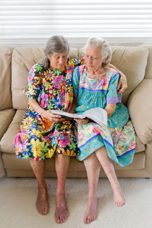 older women: Two Elderly Widows Reading A Book Stock Photo
