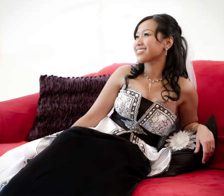 This happy bride poses in her elegant black and white wedding gown seated on her red couch.