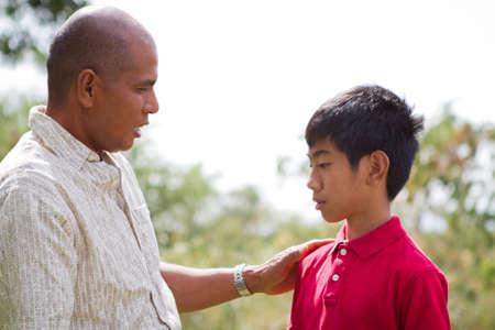padres hablando con hijos: Padre �tnica hablando con su hijo fuera. Foto de archivo