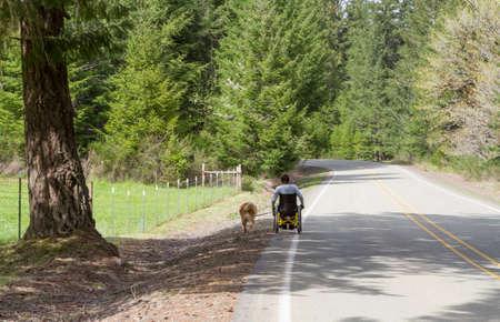 Paraplegic man taking his dog for a walk down a country road.