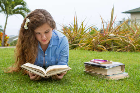 Pretty teen girl studying her school books outside in a tropical setting
