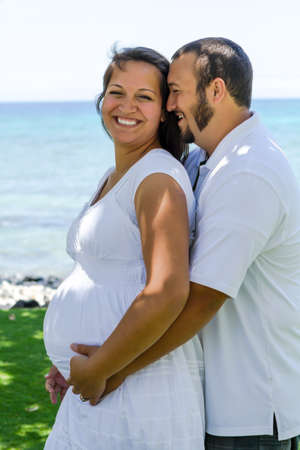 islanders: Husband whispering to his pregnant wife while holding her close next to the ocean  Stock Photo