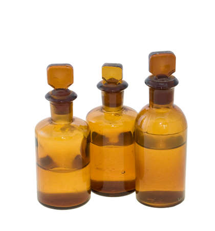 dispense: Three old fashioned chemical bottles, half full of clear liquid, isolated on white Stock Photo