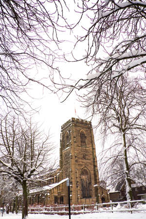 English Church in Snow, framed by branches photo