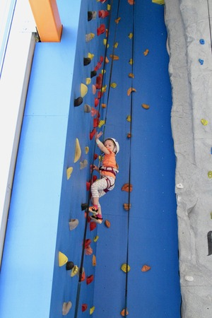 5 years old girl in helmet climbing a rock wall indoor Stock Photo