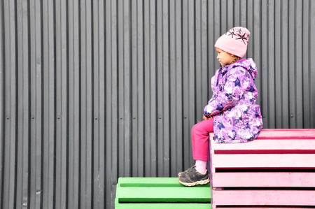 5 years old girl is sitting in front of the grey wall on colorful benches. Stock Photo