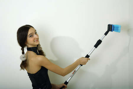 homebuyer: young smiling girl teenager use brush for washing or painting white wall Stock Photo