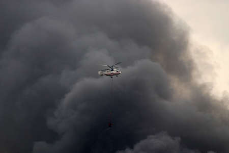 extinguishing: helicopter in a smoke carrying water on fire extinguishing