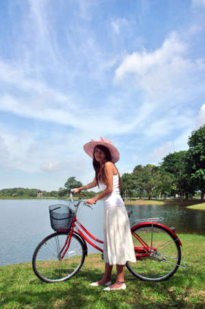 pretty girl with bicycle at the lake photo