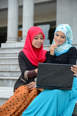 Young asian muslim woman in head scarf smile with labtop  photo