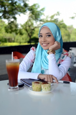 young muslim smile at cafe photo