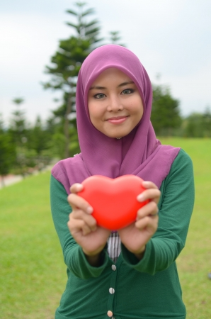 Young asian muslim woman in head scarf smile with love shape photo
