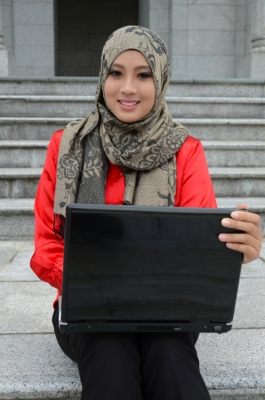 Young asian muslim woman in head scarf smile with laptop photo