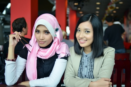 house of prayer: Close-up portrait of beautiful young Asian Muslim woman at cafe with lovely smiles