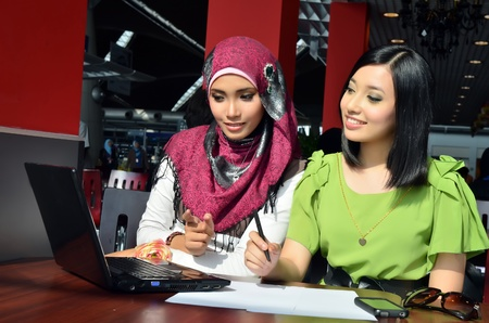 discuss: Close-up portrait of beautiful young Asian Muslim woman at cafe with lovely smiles