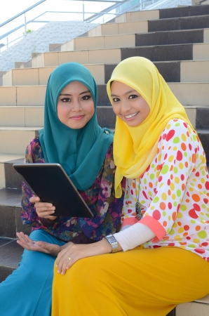 Young asian muslim woman in head scarf smile with mobile laptop  photo
