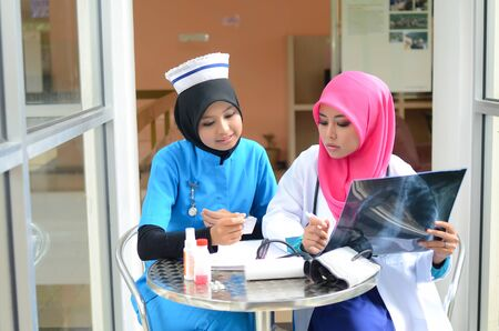 Confident Muslim female doctor and nurse in head scarf busy at work photo