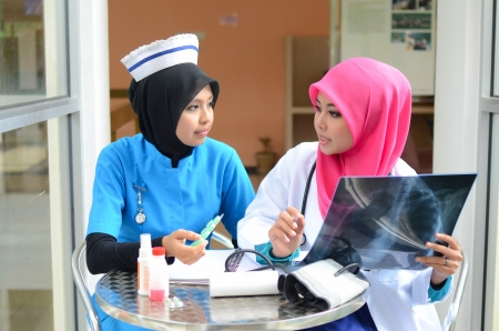 Confident Muslim female doctor and nurse in head scarf busy at work Stock Photo