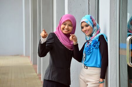 Two young Muslim woman pointing finger to something photo