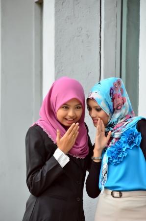 Two young Muslim woman gossiping  photo