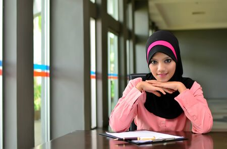 young pretty Asian muslim business woman in head scarf  photo