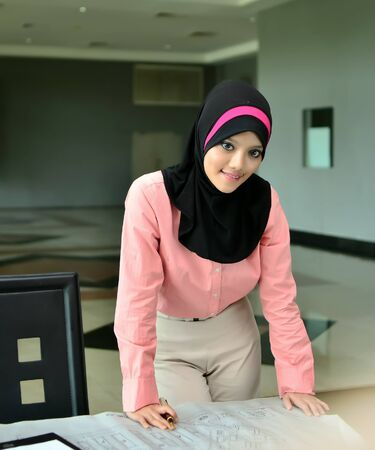 young pretty Asian muslim business woman in head scarf smile photo