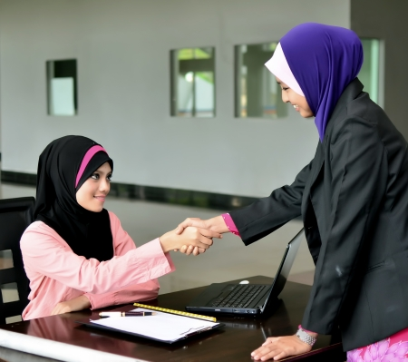 muslimah: Two young pretty Asian muslim business woman in head scarf shake hand together  Stock Photo