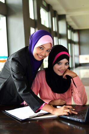 Two young pretty Asian muslim business woman in head scarf smile photo