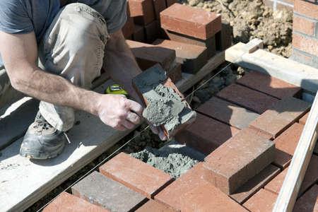 벽돌에 박격포를 적용하는 벽돌 메이슨 스톡 콘텐츠
