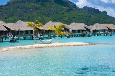 Overwater Bungalow and Hammock on Island in Bora Bora Stock Photo