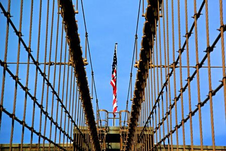 view of Brooklyn Bridge arches including US flag