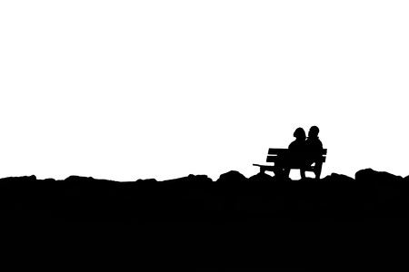 View of silhouette couple sitting on a bench Stock Photo