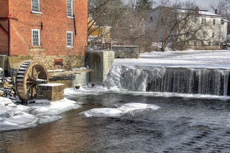 Winter river mill with wheel and ice