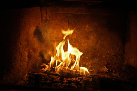 Phoenix rising from inside the flames in fireplace with logs and brick background Stock Photo