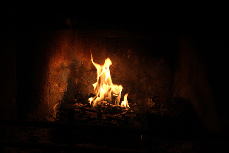 Kneeling prayer from inside the flames in fireplace
